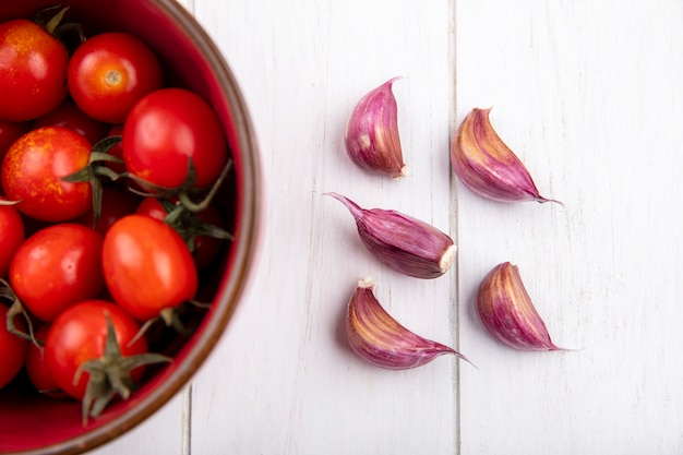 Close up view of vegetables as tomatoes in bowl and garlic cloves on wooden wall