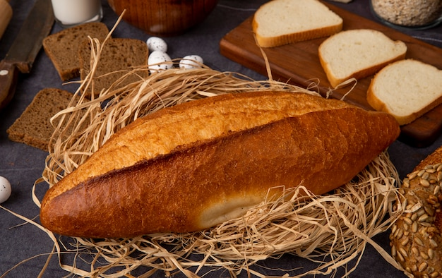 Close-up view of vietnamese baguette on straw surface with different breads on maroon background