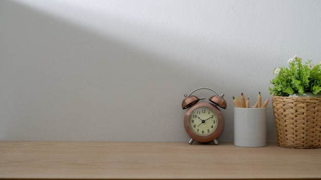 Close up view of vintage copy space with coloured pencils, tree pot and clock