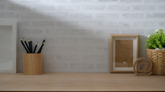 Close up view of vintage copy space with  pencils, tree pot and mock up frame on wooden table