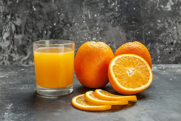 Close up view of vitamin source cut chopped and whole fresh oranges on gray background