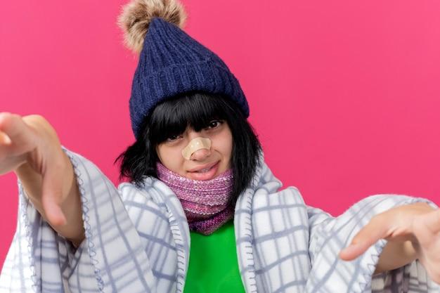 Vista ravvicinata di debole giovane donna malata che indossa cappello invernale e sciarpa avvolta in un plaid guardando davanti con intonaco sul naso che allunga le mani verso la parte anteriore isolato sul muro rosa