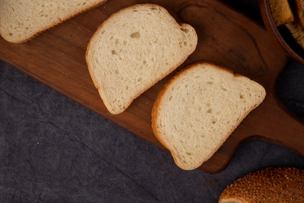 Close-up view of white bread slices on cutting board on maroon background with copy space