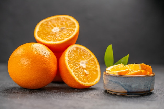 Close up view of whole and chopped fresh orange on dark table