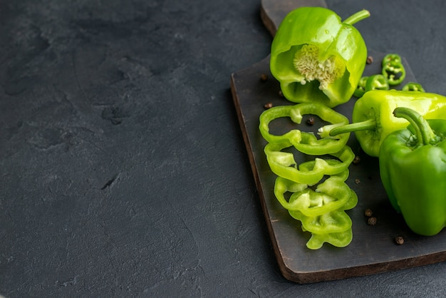 Close up view of whole cut chopped green peppers on dark color wooden cutting board on the left side on black surface