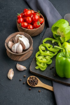 Close up view of whole cut chopped green peppers on wooden cutting board tomatoes in bowl garlics on dark color towel on black surface