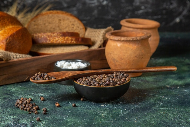 Close up view of whole and cut fresh black bread on towel in a brown wooden box potteries spices on dark mix colors surface