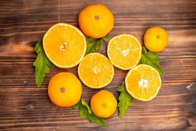 Close up view of whole and cut fresh oranges with leaves on a brown background