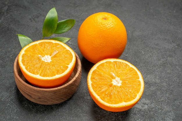 Close up view of whole and cut fresh oranges with leaves on dark table