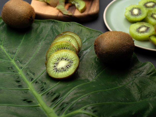 Close up view of whole and sliced kiwi fruits on green leaf in kitchen room