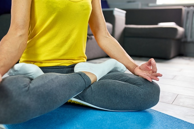 Close up view of woman doing morning yoga at home, in lotus position.