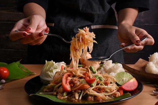 Крупным планом вид женщина ест острый салат из папайи.