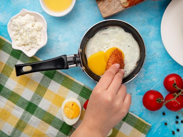 Vista del primo piano della mano della donna che mangia uovo fritto con il pepe nero del pomodoro della ricotta sul blu