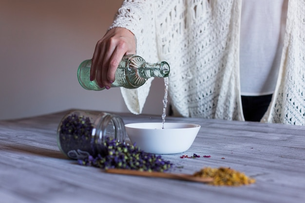 Close up view of a woman hand spreading water in a bowl with roses. spoon with yellow turmeric and a bowl with purple dried leaves on the table. casual clothing. indoors and healthy lifestyle