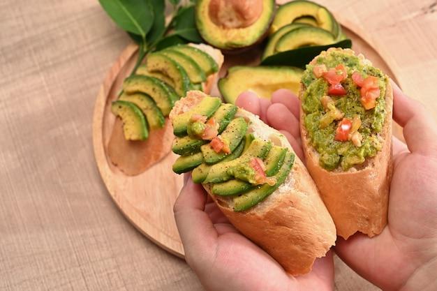 アボカドサンドイッチを保持している女性をクローズアップします。