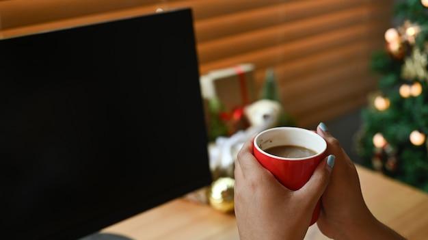 ホットコーヒーのカップを保持している女性をクローズアップします。