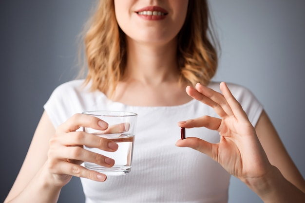 Close up view of woman holding glass of water and a pill. health treatment, medication.