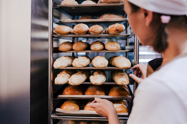 Close up view of woman holding holding rack of rolls in a bakery.
