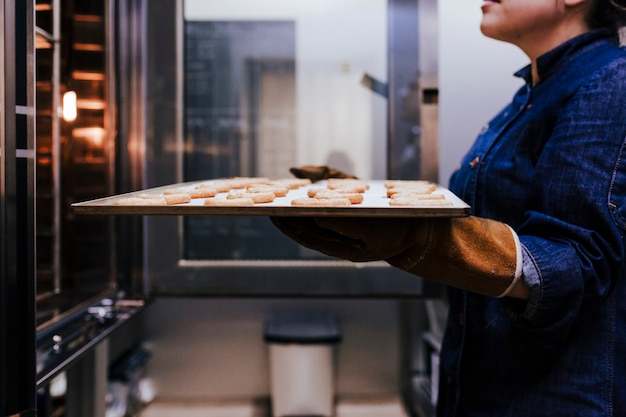 Close up view of woman holding holding rack of sweets in a bakery.