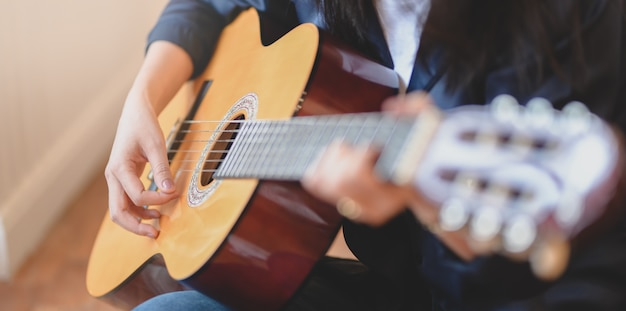 Close-up view of woman playing acoustic guitar in comfortable room