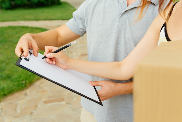 Close-up view of woman putting a signature in clipboard for delivery man