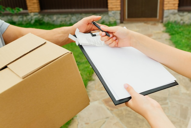 Close-up view of woman putting a signature on paper after getting a shipping package. home delivery service, outdoors.