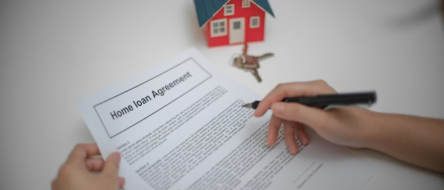 Close up view of a woman reading home loan agreement to consider before sign contract