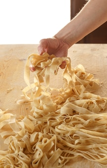 Close-up view of woman's hand pulling up fresh fettuccine on wooden work table in natural sunlight