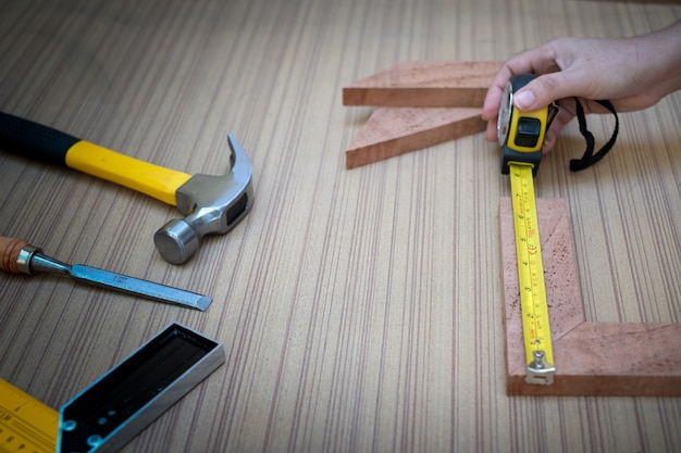 Close up view of a woman's hands measuring wooden plank with a tape measure with a set collection of working hand tools for the wooden, toolset with the do it yourself (diy)
