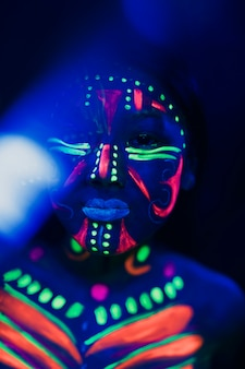 Close-up view of woman with colorful fluorescent make-up