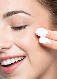 Vista ravvicinata della donna con crema sulle dita
