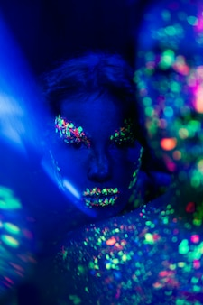 Close-up view of woman with fluorescent make-up
