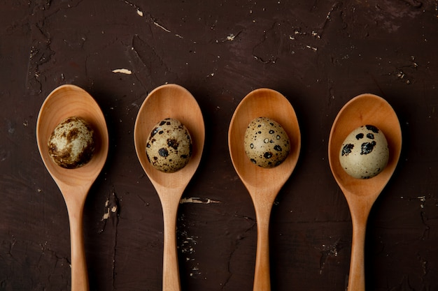 Close-up view of wooden spoons with eggs on maroon