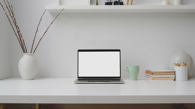 Close up view of workplace with blank screen laptop, books, decorations on white desk
