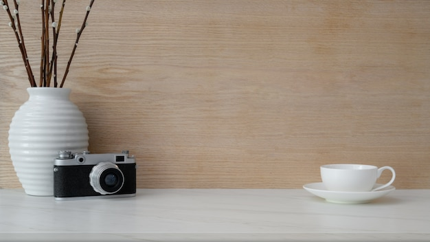 Close up view of workplace with copy space, coffee cup, camera and ceramic vase