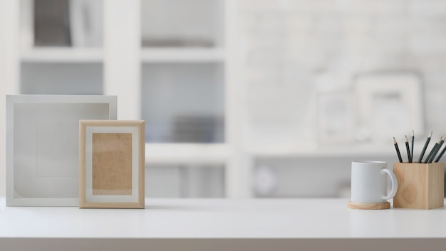 Close up view of  workplace with copy space,  frames, pencils and coffee cup on white table
