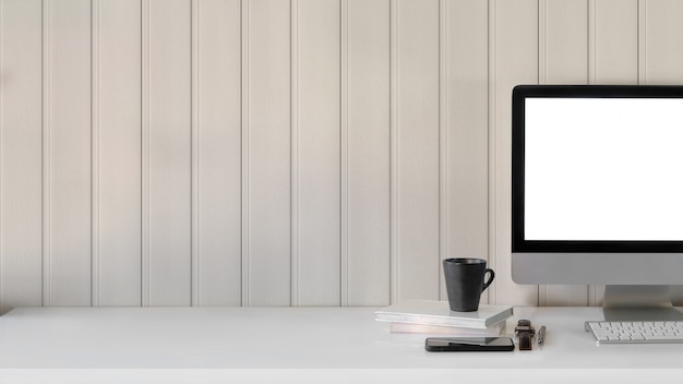 Close up view of workspace with blank screen computer, , coffee cup and office supplies on white table with plank wall