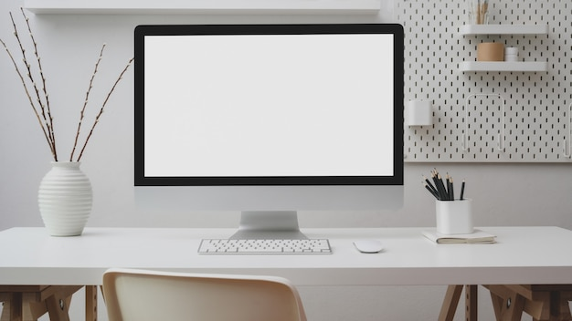 Close up view of workspace with blank screen computer, office supplies, decoration and shelf on white desk with white wall