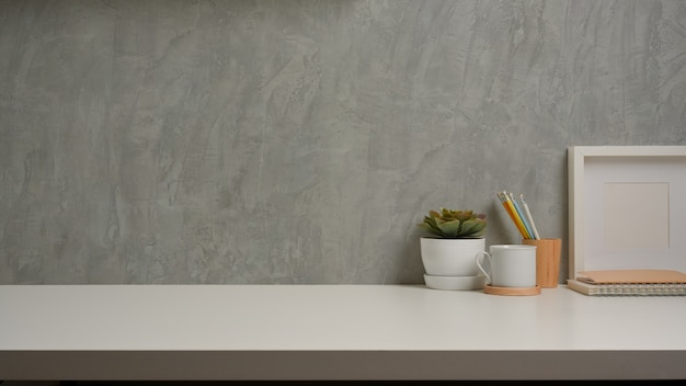 Close up view of workspace with decorations and copy space on white table with loft wall background