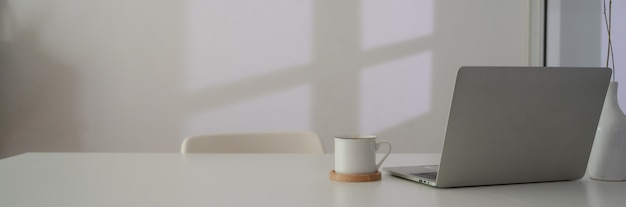 Close up view of workspace with laptop, coffee cup and copy space on white table next to window