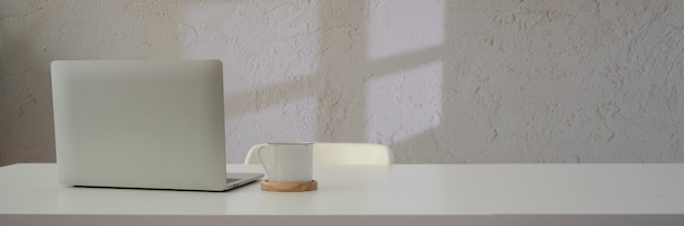 Close up view of workspace with laptop, coffee cup and copy space on white table