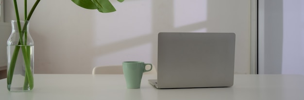 Close up view of workspace with laptop, mug and plant vase on white table next to window