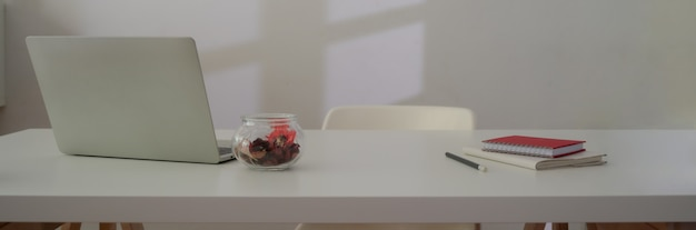 Close up view of workspace with laptop, supplies, decoration and copy space on white table