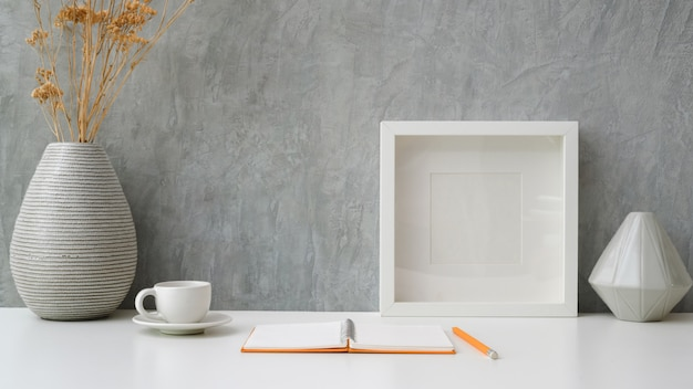 Close up view of workspace with open notebook, coffee cup,  frame and ceramic vases on white table with grey loft wall