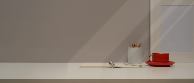 Close up view of workspace with stationery, coffee cup, mock up frame and copy space on white table