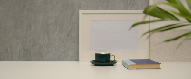 Close up view of worktable with cup, book, mock up frame, plant vase and copy space in living room
