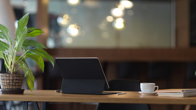 Close up view of worktable with digital tablet, coffee cup, notebooks and plant pot in office room