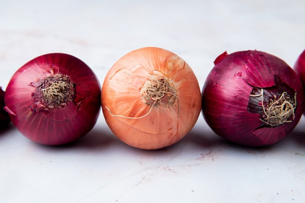 Close-up view of yellow and red onions on white background