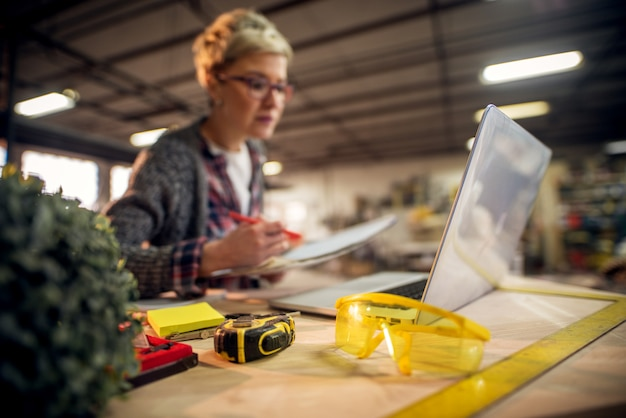 Close up view of yellow workshop glasses in front of female engineer with eyeglasses working with blueprints and laptop in the workshop