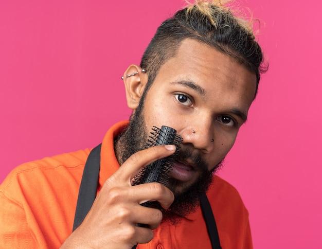 Vista ravvicinata del giovane barbiere maschio afroamericano che indossa l'uniforme che si pettina i baffi